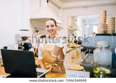 Caucasian attractive woman barista smiling at the counter bar, suggesting coffee cup in a modern cafe or restaurant. #1466364848