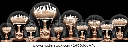 Large group of light bulbs with shining fibers in a shape of Inspiration, Creativity, Strategy, Innovation and Idea concept related words isolated on black background; horizontal composition #1466368478