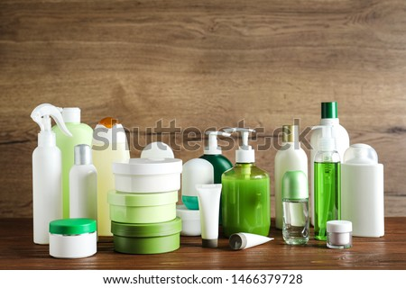 Different body care products on table against wooden background Royalty-Free Stock Photo #1466379728