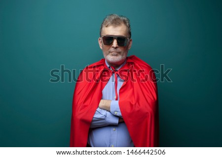 Portrait of a confident senior man in a superhero costume on a green background. The concept of an omnipotent man. Advertising space #1466442506