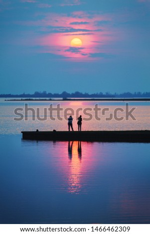 A romantic sunset with people on a jetty at the lake together watching the sun setting on a colorful and warm summers evening - lifestyle image