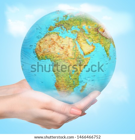 We live here everyday. People of the Earth advocate for preservation of nature and life on the planet. Eco problems or concept of trave, discovering new places. Female hands holding a globe caressly. #1466466752
