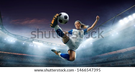 Female Soccer player in action on a professional soccer stadium. Girl playing soccer #1466547395