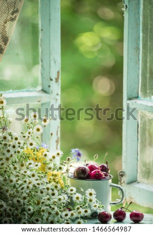 Summer simple still life. Sweet cherry in an iron mug on the old window overlooking the garden. Vintage style. summer on the farm.  #1466564987