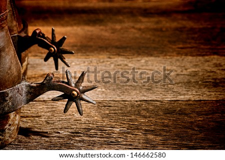 American West rodeo vintage riding spurs with sharp spikes rowel on authentic western cowboy traditional leather boots on old aged wood background in an antique ranching barn