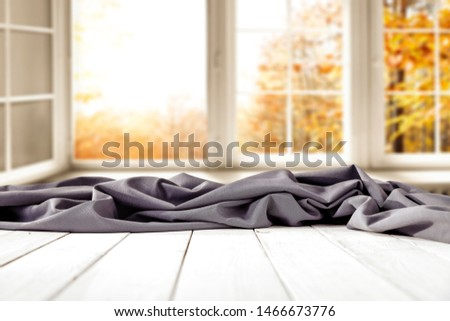 White wooden table background with grey cloth and autumn outside the window. Empty space for advertising products and decoration. #1466673776