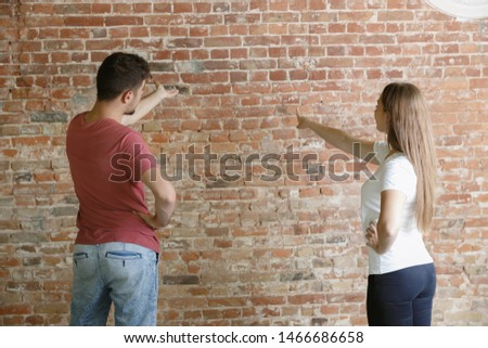 Young couple doing apartment repair together themselves. Married man and woman doing home makeover or renovation. Concept of relations, family, love. Discuss painting the wall or preparing it for. #1466686658