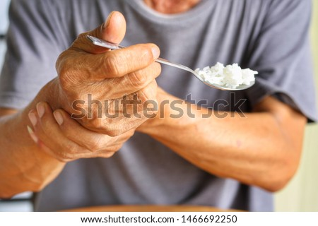 Elderly man is holding his hand while eating because Parkinson's disease.Tremor is most symptom and make a trouble for doing activities such as eat.Health care or elderly concept.Selective focus. #1466692250