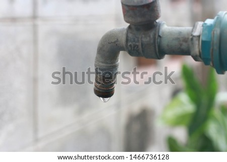 Water drop falling from an old tap #1466736128