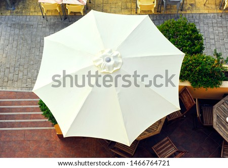 White umbrella seen from above on the terrace of a beach bar Royalty-Free Stock Photo #1466764721