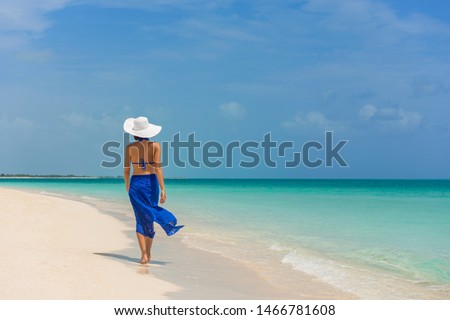 Luxury travel woman walking on perfect beach vacation Caribbean destination in blue dress skirt sarong. Elegant lady tourist relaxing on summer vacations wearing sun hat. #1466781608