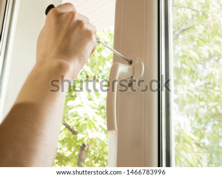 a man fixes a window, fastens a handle close up #1466783996