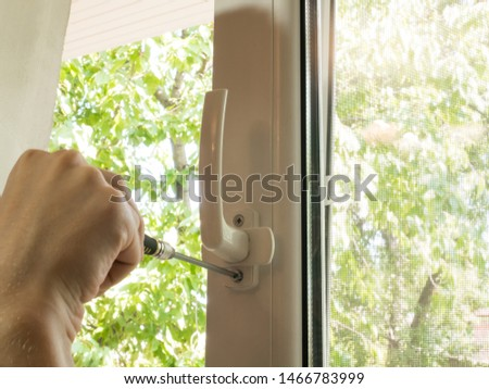 a man fixes a window, fastens a handle close up #1466783999