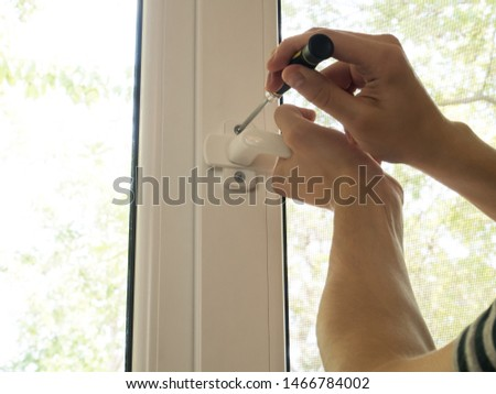 a man fixes a window, fastens a handle close up #1466784002