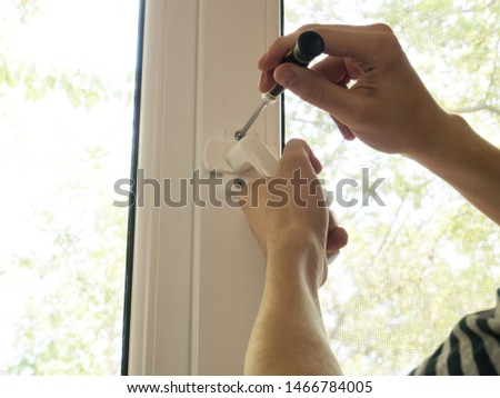 a man fixes a window, fastens a handle close up #1466784005