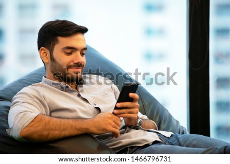 Portrait of Smiling Businessman using smartphone while sitting on sofa at his home.young people working on mobile devices, business technology lifestyle concept  #1466796731