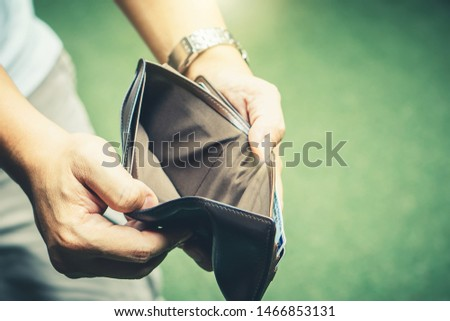 Poor man bankrupt with no credit in debt hand hold empty black leather wallet because economy down turn depression crisis fail working saving finance money plan loss job unemploy. No money to pay #1466853131