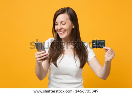 Portrait of cheerful young woman in white casual clothes using mobile phone, holding credit bank card isolated on yellow orange wall background in studio. People lifestyle concept. Mock up copy space #1466905349