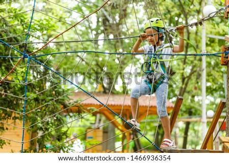 Happy school girl enjoying activity in a climbing adventure park on a summer day #1466936354