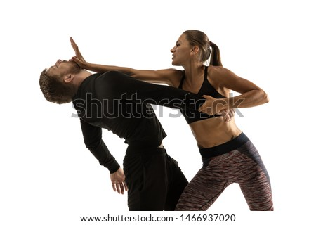 Man in black outfit and athletic caucasian woman fighting on white studio background. Women's self-defense, rights, equality concept. Confronting domestic violence or robbery on the street. Royalty-Free Stock Photo #1466937020