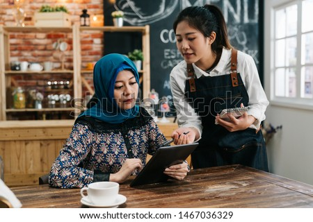 Young Asian waitress advising islam woman client to choose new snack from menu on mobile pad in restaurant. girl coffee shop staff taking order of muslim lady customer in cafe bar for lunch meal. #1467036329