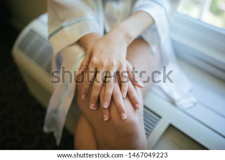 Bride with crossed hand and legs sitting on a window in a hotel room. Closeup of a ring. #1467049223