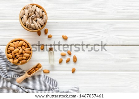 Almond in bowls for cooking oil on white wooden background top view mockup #1467057461
