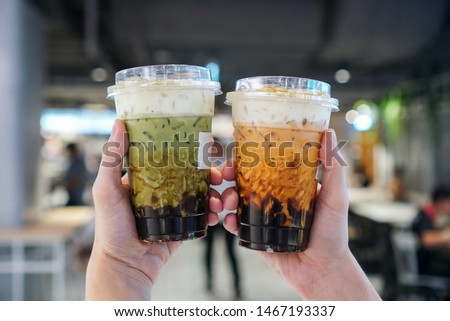 Matcha Green tea and Thai Tea Bubble drinks, man holding a plastic cup of bubble/boba matcha green tea and Thai tea with brown sugar and topped with cheese cream. #1467193337