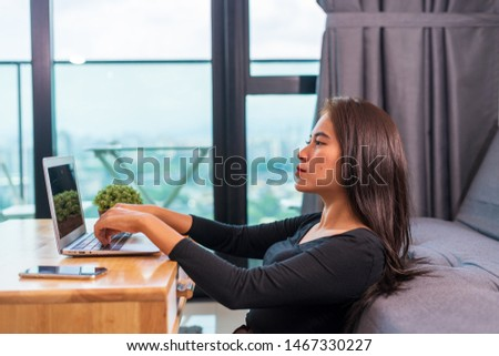 Portrait of young Asian woman focus, typing on her laptop, doing work at home, sitting on floor. #1467330227