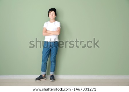 Stylish boy in jeans near color wall #1467331271