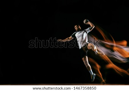 Caucasian young handball player in action and motion in mixed lights over black studio background. Fit male professional sportsman. Concept of sport, movement, energy, dynamic, healthy lifestyle. #1467358850