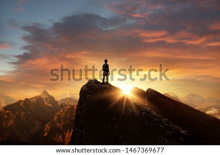 A man standing on top of a mountain as the sun sets. Goals and achievements concept photo composite. Royalty-Free Stock Photo #1467369677