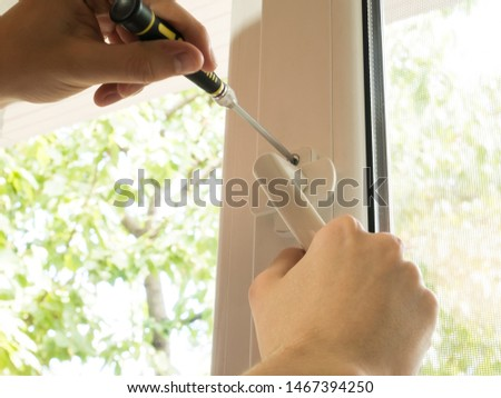 a man fixes a window, fastens a handle close up #1467394250