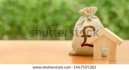Wooden house figurine and pound sterling money bag on the background of nature. Budget, subsidized funds. Mortgage loan for purchase housing, construction or modernization. Tax, building maintenance. #1467505382