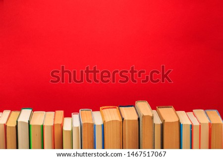 Simple composition of hardback books, raw of books on wooden deck table and red background - Image  #1467517067