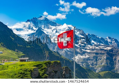 Swiss flag waving and tourists admire the peaks of Monch and Jungfrau mountains on a Mannlichen viewpoint, Bernese Oberland Switzerland #1467524654