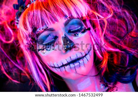 Close-up portrait of an attractive woman with sugar skull makeup in bright blacklight bodyart #1467532499