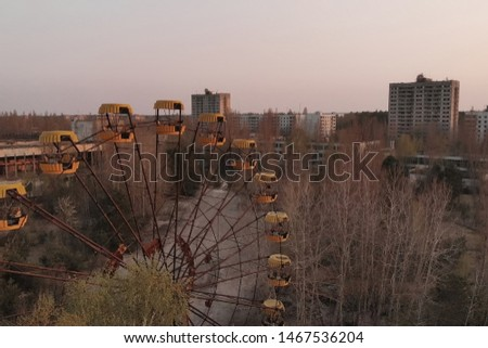 Rusty ferris wheel in the amusement park of the city of Pripyat. Ferris wheel in the City of Pripyat at sunset time. Apocalyptic city of Pripyat after a nuclear explosion at a nuclear power plant. #1467536204