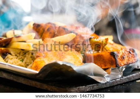 Delicious paneer, french fries and vegetble sizzler giving off smoke and steam. This dish is a favorite in north india and comes in vegetarian and non vegetarian variants and various ingridients #1467734753
