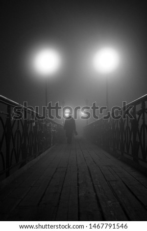 lonely man walks at night on a bridge in the fog #1467791546