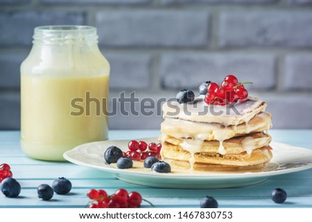 Pancakes with condensed milk and berries. Tasty breakfast with blueberries and currants. Delicious healthy food. Photo of a fresh natural dessert. Royalty-Free Stock Photo #1467830753