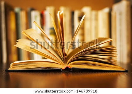 Hardcover book lying open on its cover with the pages fanned above it and a row of books on a bookshelf visible behind, shallow dof #146789918