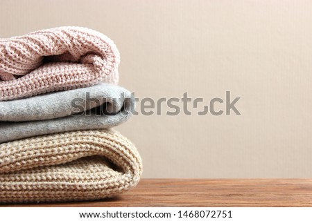 A pile of warm sweaters on a wooden table on a color background. Autumn and winter clothes.  #1468072751