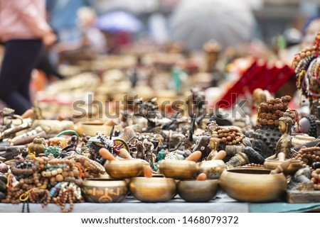 (Selective focus) Close-up view of some souvenirs (singing bowls, hand created statues and Rudraksha necklace) on a street market stall in Kathmandu Durbar Square, Kathmandu, Nepal. #1468079372