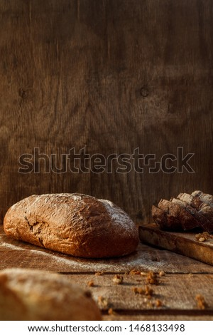 Freshly baked wheat bread, homemade cakes, still life with bread, crisp loaf of bread, still life on a rustic background, top view, rustic bread, roll, loaf. #1468133498