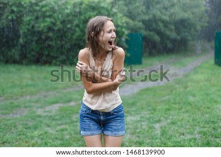 Happy smiling woman under summer rain.emotional girl wet in the rain without umbrella.woman walk in the rain.young attractive woman is wet in the rain #1468139900