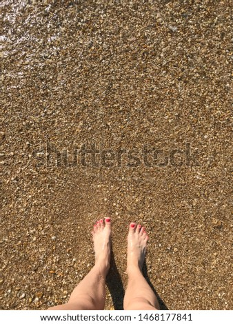 Female legs with bright pedicure pebble beach and sea wave #1468177841