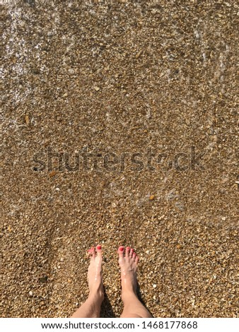 Female legs with bright pedicure pebble beach and sea wave #1468177868