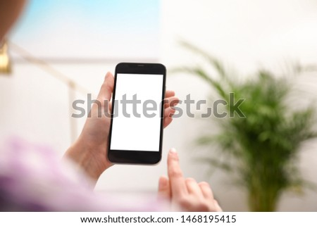 Woman holding smartphone with blank screen indoors, closeup of hands. Space for text #1468195415