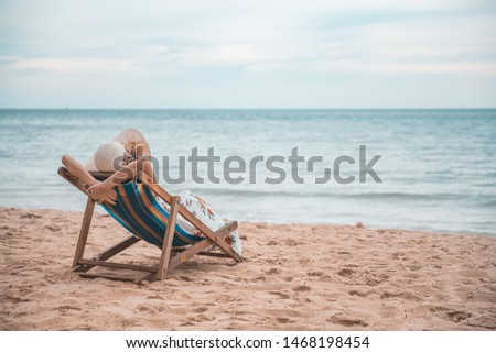 Summer beach vacation concept, Happy young Asian woman with hat relaxing on beach chair and raised hands up. #1468198454